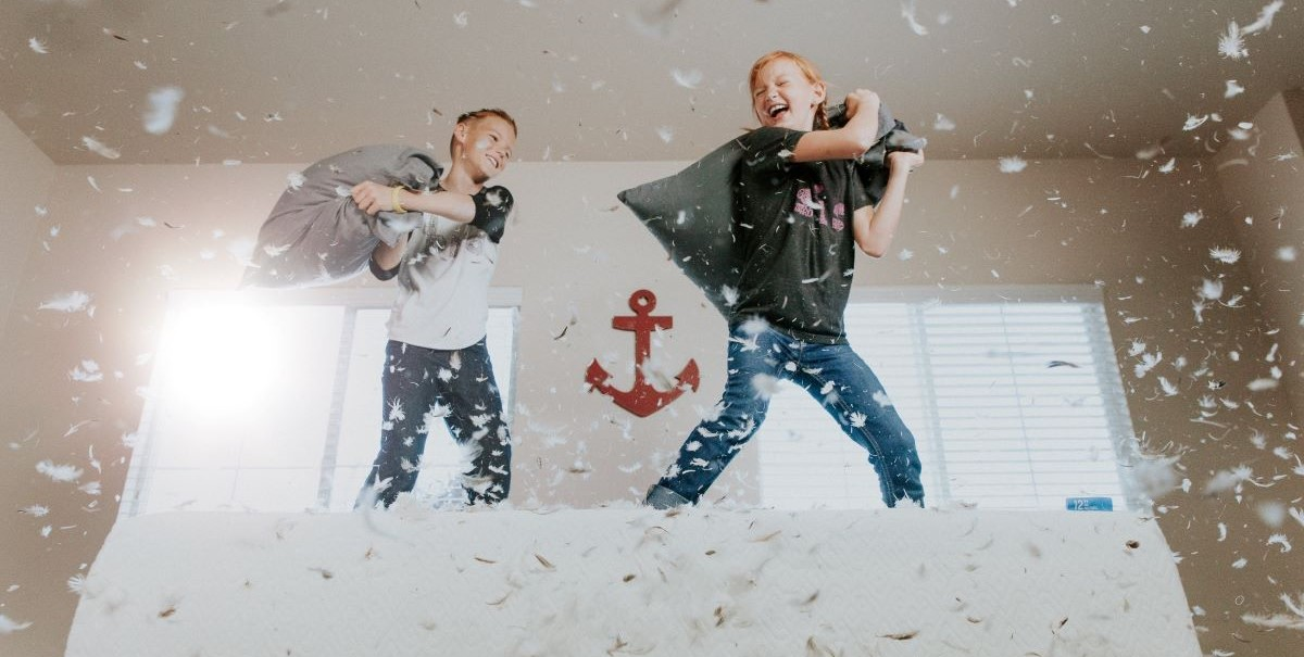 Two toddlers have a pillow fight and laugh as feathers fly around them.